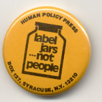 "Yellow pin-button with a drawing on a jar in black marked ""Label Jars ... Not People"" and the Human Policy Press address"