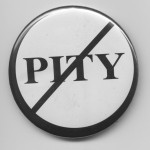 """White pin-button printed """"Pity"""" in black, with a black circle around it and a black line through it"""